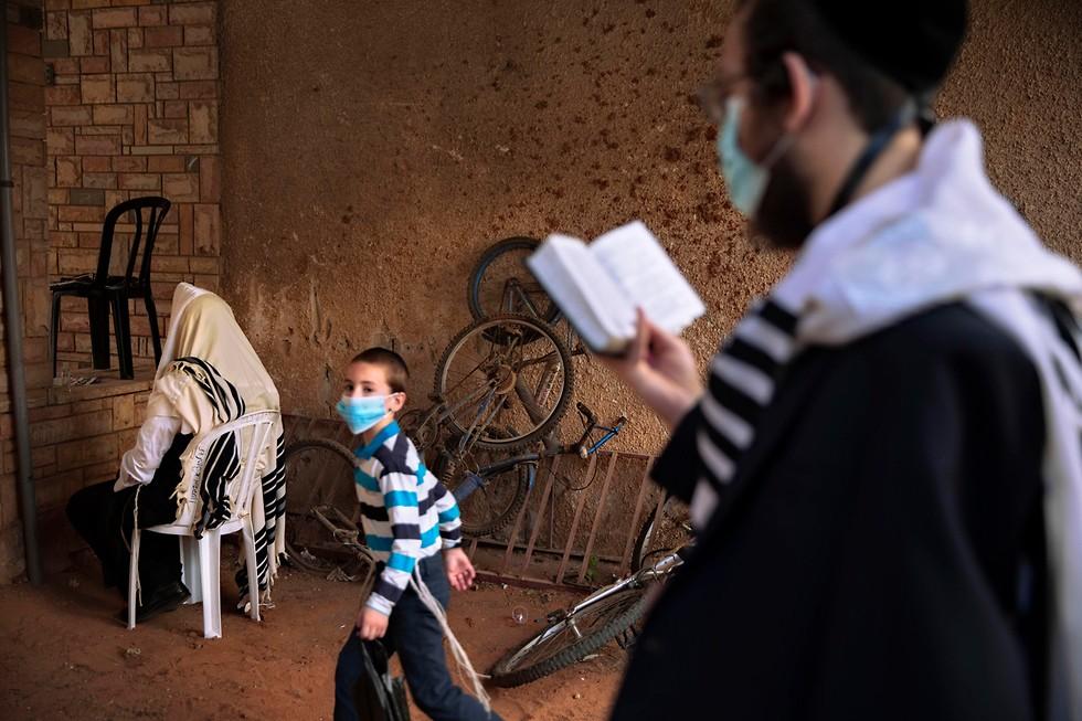 Judíos ultraortodoxos rezan afuera de una sinagoga en Bnei Brak.
