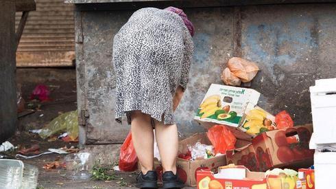 Una escena de Tel Aviv: una mujer revuelve la basura en busca de comida.