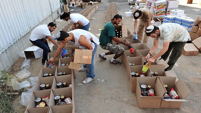 Voluntarios israelíes trabajan en la distribución y separación en un banco de alimentos.