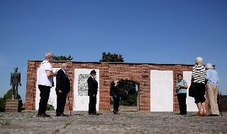 Los visitantes se paran frente a los restos del granero de campo en el sitio conmemorativo.