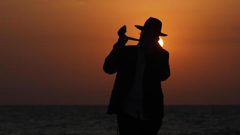 Un hombre ultraortodoxo toca el shofar en una playa de Tel Aviv durante el cierre general.