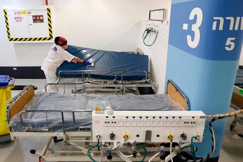 """Una empleada del hospital Rambam prepara las camas para recibir a los pacientes en la nueva """"ala covid"""" del hospital Rambam."""