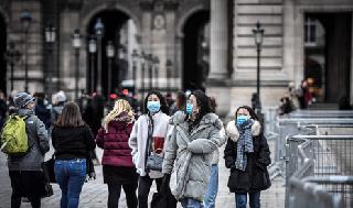 Turistas usan barbijos de protección fuera del Museo del Louvre, en París, Francia.