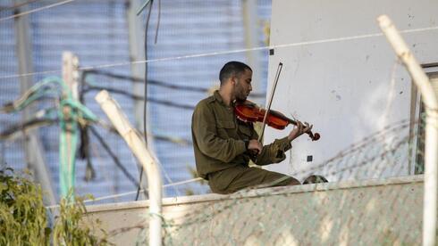El sargento Yitzhak Eliezer y su violín en el cruce Rosh Hanikrá.