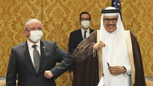 El jefe del Consejo de Seguridad Nacional de Israel, Meir Ben-Shabbat, saluda con el codo al ministro de Relaciones Exteriores de Bahrein, Abdullatif al-Zayani, después de firmar un acuerdo en Manama.