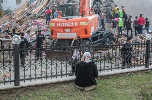 Uma mulher ora enquanto a equipe de resgate trabalha nos escombros.