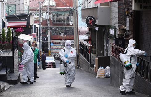 Trabajadores de la salud de Corea del Sur desinfectan una calle en Seúl.