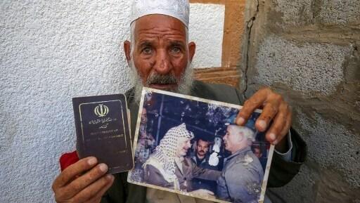 Abu Hashem enseña una de sus fotos junto a Yasser Arafat.