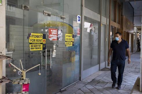 Un hombre pasa junto a un negocio cerrado en Jerusalén durante la pandemia.
