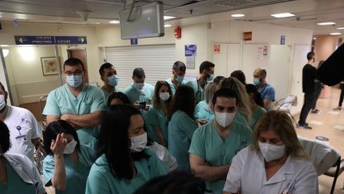 Membros da equipe médica do Hospital Ichilov de Tel Aviv fazem fila para receber a vacina COVID-19.