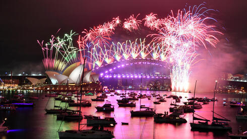 Fuegos artificiales explotan sobre la Ópera y el Puente del Puerto, en Sídney, durante las celebraciones de Año Nuevo.