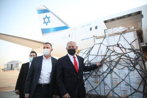 El ministro de Salud Yuli Edelstein y el primer ministro Benjamín Netanyahu reciben el segundo cargamento de vacunas de Pfizer en la pista del Aeropuerto Ben Gurion.