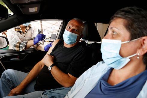 Una persona recibe la vacuna adentro de su automóvil.