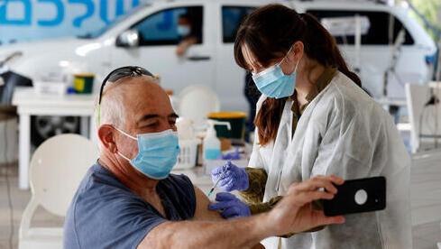 Una de las personas con prioridad para la inoculación recibe su dosis en Haifa.