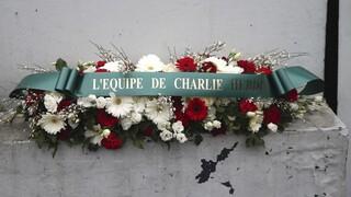 "Corona de flores de la revista Charlie Hebdo frente al supermercado ""Hyper Cacher"" de París."