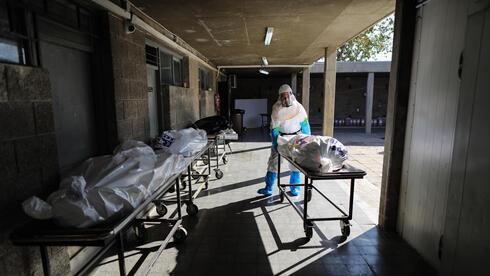 Trabajadores de Chevra Kadisha con equipo de protección se preparan para el entierro en el cementerio de Holon de personas fallecidas por COVID-19.