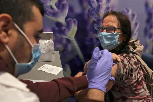 Mujer israelí es vacunada en un centro médico de Jerusalem.