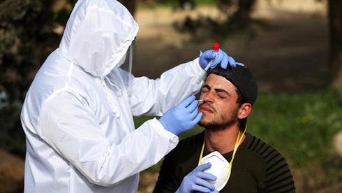 Trabajador palestino se realiza test de COVID-19 al regresar de Israel.