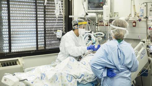 Personal médico atiende a un paciente en la sala de coronavirus del Centro Médico Hillel Yaffe en Hadera.