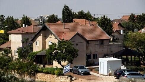 Una bandera israelí flamea cerca de un grupo de casas en el asentamiento de Otniel en Cisjordania. q