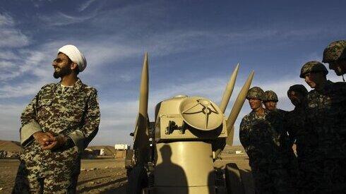 Un clérigo iraní junto a misiles y soldados del ejército en Irán.
