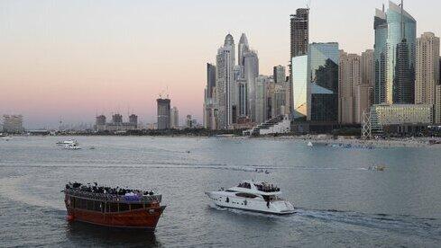 A la izquierda, un crucero que vende a los turistas un show con cena; y a la derecha, otro yate con turistas, en Dubai.