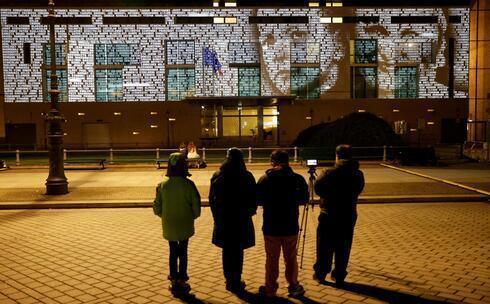 As pessoas observam uma instalação leve chamada #everynamecounts (cada nome conta) que projeta os nomes das vítimas do regime nazista na fachada da embaixada francesa para lembrar as vítimas antes do Dia de Comemoração do Dia Internacional de Comemoração em Memória das Vítimas do Holocausto em Berlim, Alemanha.