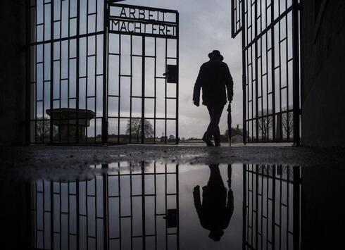Um homem entra pela porta do campo de extermínio nazista em Sachsenhausen durante o Dia Internacional de Comemoração em Memória das Vítimas do Holocausto, em 2019.