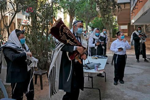 Ultraortodoxos rezan al aire libre en Bnei Brak para cumplir con las restricciones sanitarias.