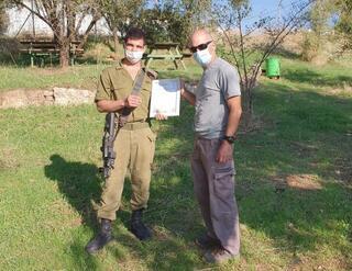 El soldado Ido Gerdi recibe un certificado de buen ciudadano por el hallazgo de la moneda.