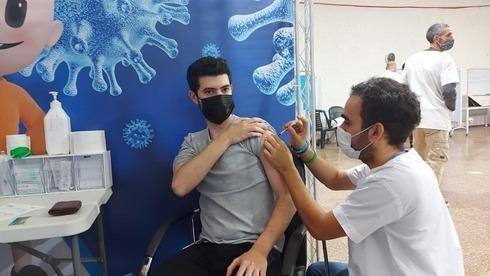 Un estudiante de secundaria recibe la vacuna contra el coronavirus en Givatayim después de que Israel incluyera a todos los mayores de 16 años en la campaña de vacunación.