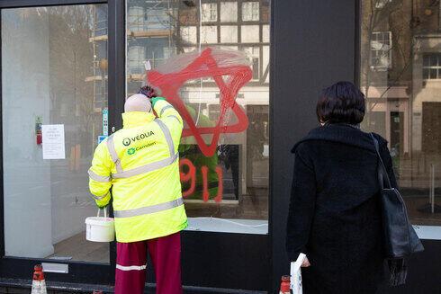 Un trabajador municipal borra un graffiti antisemita en un comercio judío de Londres.