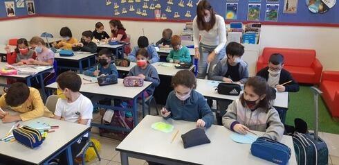 Niños en clase, usando mascarilla de protección.