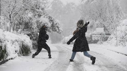 As crianças brincam na neve no kibutz Merom Golan.