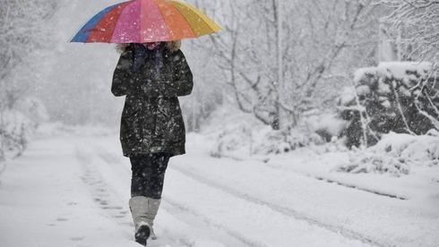 Uma mulher caminha sob a tempestade de neve no kibutz Merom Golan.