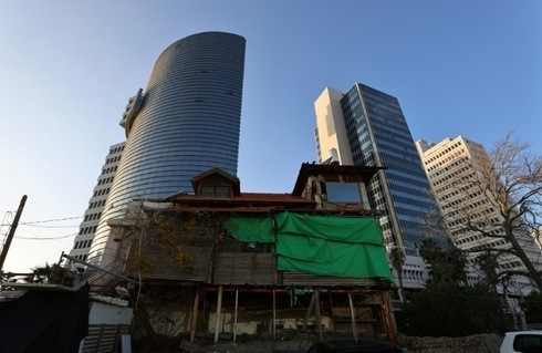 Una antigua casa de madera se encuentra frente a edificios modernos en Tel Aviv.