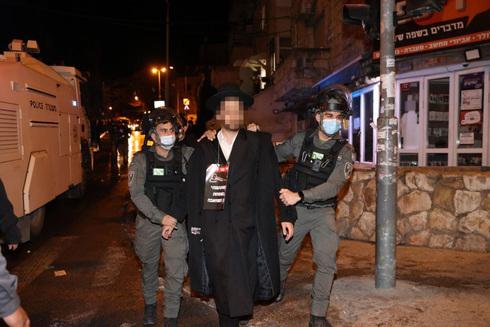Agentes de policía arrestan a un hombre ultraortodoxo durante una protesta contra las restricciones del COVID-19 en Bnei Brak.