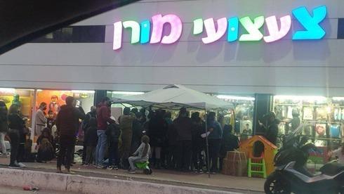 Largas filas en una juguetería para comprar disfraces de Purim.