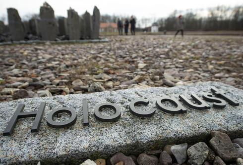 La gente camina detrás de la escritura 'Holocausto' durante el día internacional del recuerdo del Holocausto en el antiguo campo de concentración nazi de Buchenwald.