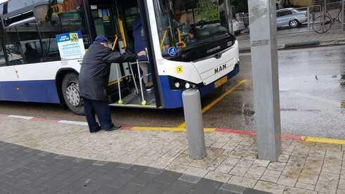 Un anciano israelí intentando abordar el transporte público.