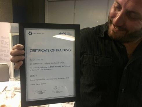 Un joven chileno recibe un certificado de capacitación en gestión de crisis comunitaria.