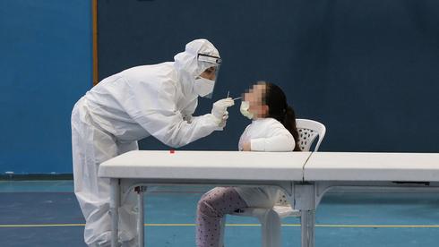 Personal de salud realiza una prueba para detectar coronavirus a una niña en Beit Shemesh.