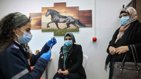 Una mujer palestina recibe su vacuna contra el coronavirus en el puesto de control de Qalandia entre Jerusalem y Cisjordania.