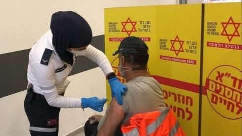 Uno de los trabajadores palestinos recibe su dosis de vacuna contra el coronavirus.