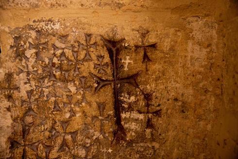 Las cruces grabadas en el antiguo muro de piedra de la capilla de Santa Elena en la Iglesia del Santo Sepulcro en Jerusalem.