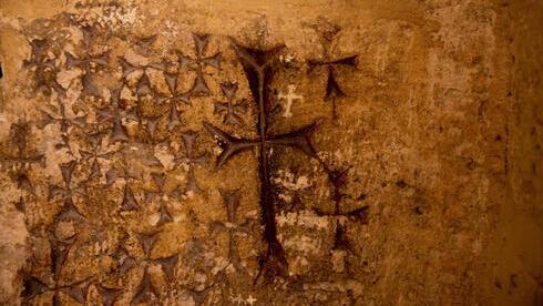 El padre Samuel Aghoyan, el superior armenio de la Iglesia del Santo Sepulcro sostiene velas para iluminar las cruces grabadas en el antiguo muro de piedra de la capilla de Santa Elena.