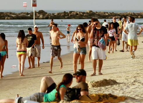 Israelíes toman sol en la playa de Tel Aviv.