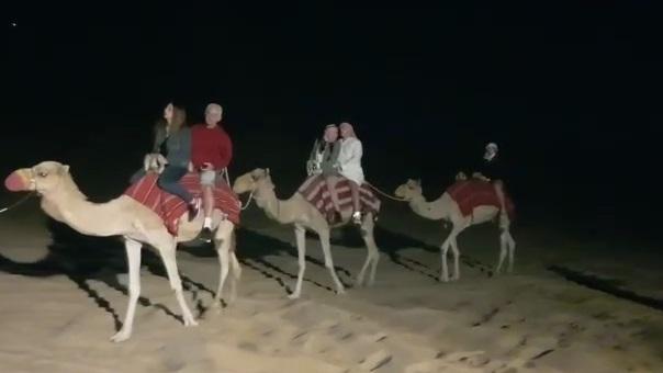 Turistas israelíes disfrutan de un paseo en camello por el desierto de Dubai.