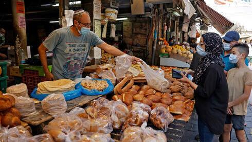 En el Mercado Mehane Yehuda, de Jerusalem, tanto comerciantes como clientes usan mascarillas protectoras al aire libre.