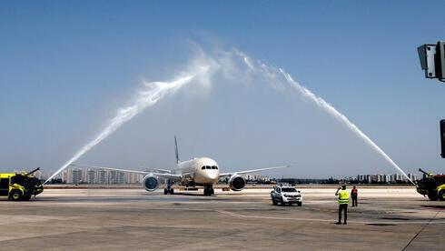 """Un saludo de agua da la bienvenida a un avión Boeing 787-9 """"Dreamliner"""" de Etihad Airways después de aterrizar a su llegada desde los Emiratos Árabes Unidos."""